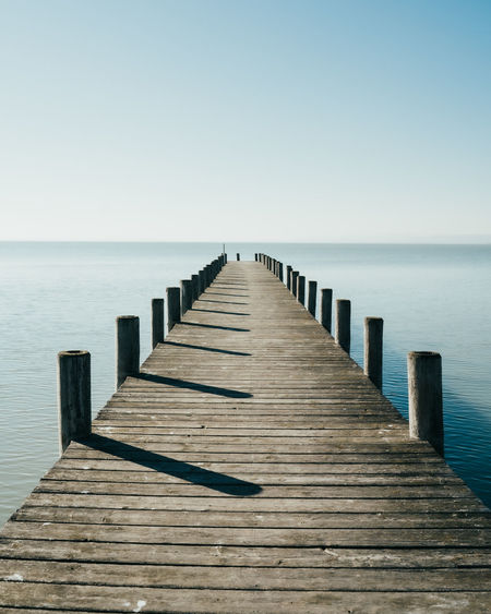 Wooden pier on sea against clear sky