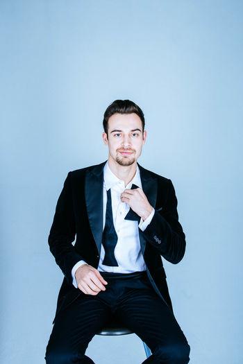 Portrait of businessman gesturing against blue background