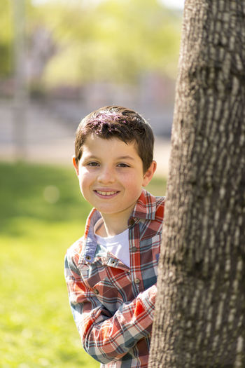 Outdoor portrait of a cheerful Young boy Boys Child Childhood Day Happiness Innocence Leisure Activity Looking At Camera Males  Men Nature Offspring One Person Outdoors Plant Portrait Smiling Tree Tree Trunk Trunk