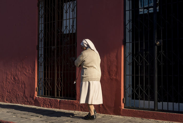 Nun walking in the street Alone Believer Church Convent Creative Light And Shadow Cross Faith Nun Nunnery Paving Stone Praying Red Wall Religion Shadow Sidewalk Street Street Photography Sunlight Sunlight And Shadow Walking Wrought Iron Gates