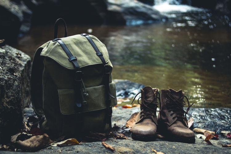 Close-up of backpack and boots on rock against river