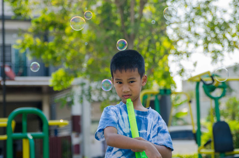 Portrait of boy playing with bubbles against trees