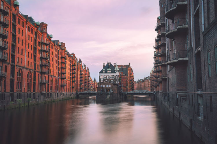 View of building by canal during sunset