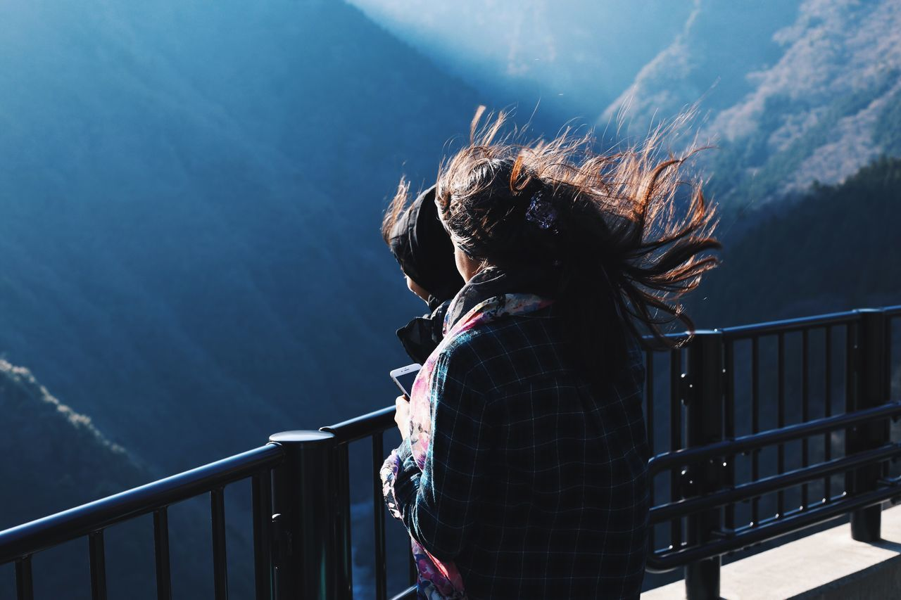 Female friends with tousled hair standing by railing against mountains