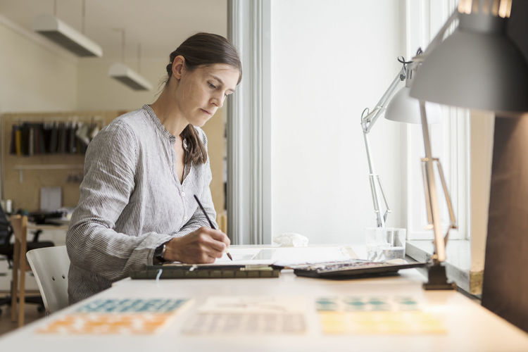 Woman looking at camera while sitting on table at home