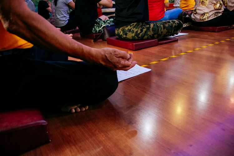 Real People Sitting Group Of People Low Section Indoors  Flooring Men People Wood Human Body Part Lifestyles Hardwood Floor Relaxation Human Hand Spirituality Yoga Human Leg Hand Leisure Activity