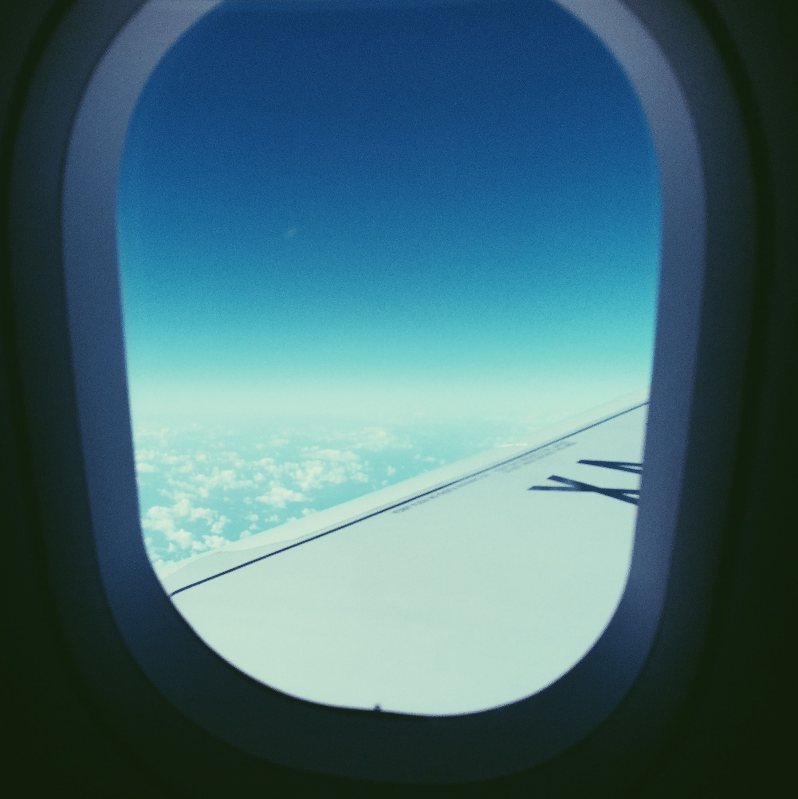 window, low angle view, transportation, indoors, glass - material, sky, transparent, clear sky, built structure, blue, part of, connection, airplane, architecture, copy space, no people, vehicle interior, cropped, day, flying