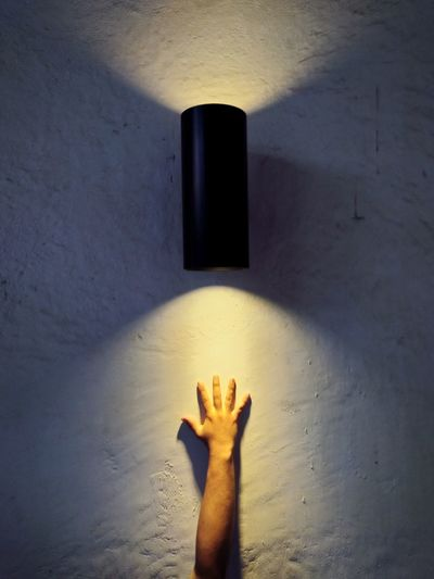 Low section of person with shadow on wall