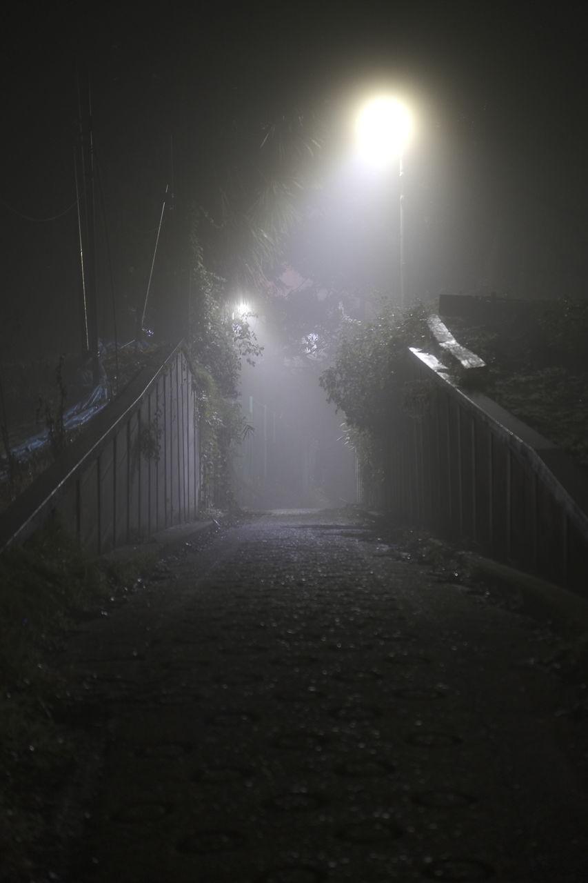 STREET LIGHT ON FOOTPATH BY RAILING AT NIGHT