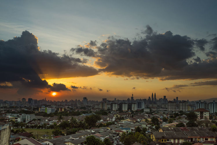 Cityscape against cloudy sky during sunset