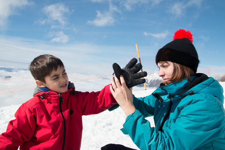 Mother helping son in wearing glove on snow against sky