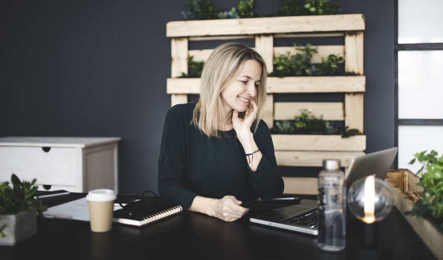 Smiling businesswoman looking at laptop in office