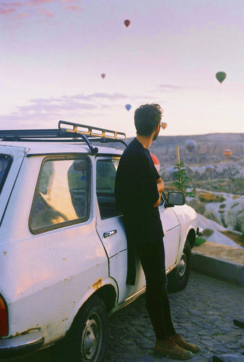 Side View Of Man Standing By Car Against Hot Air Balloons In Sky