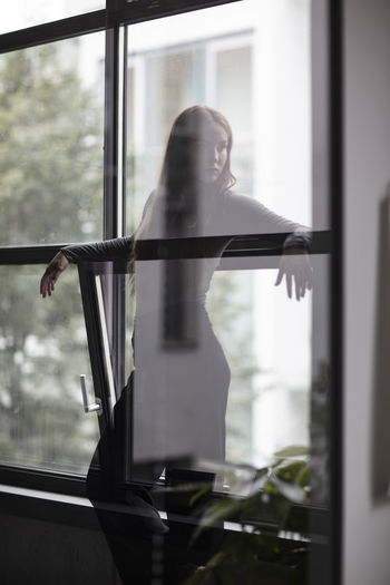 Thoughtful young woman standing by windows