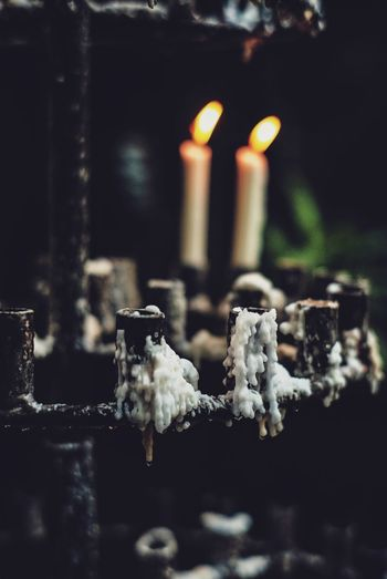 Close-up of lit candles in cemetery