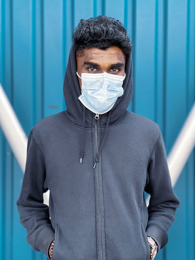 Portrait of young man wearing mask standing against wall