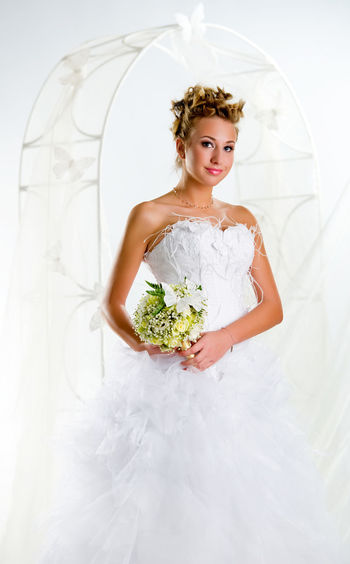 Portrait Of Smiling Bride Holding Bouquet While Standing Against Arch