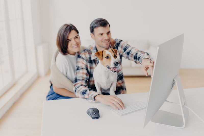Couple working on desktop pc at home
