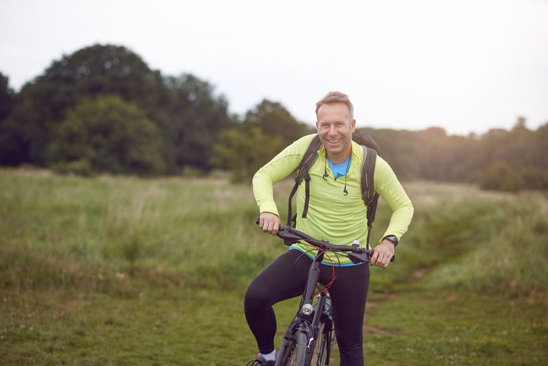 Smiling mature man on bicycle tour Copy Space Man Active Activity Adventure Bike Countryside Cycling Exploration Grassland Healthy Lifestyle Lifestyles Mature Adult Middle-aged Outdoors Real People Sports Tour Tourism