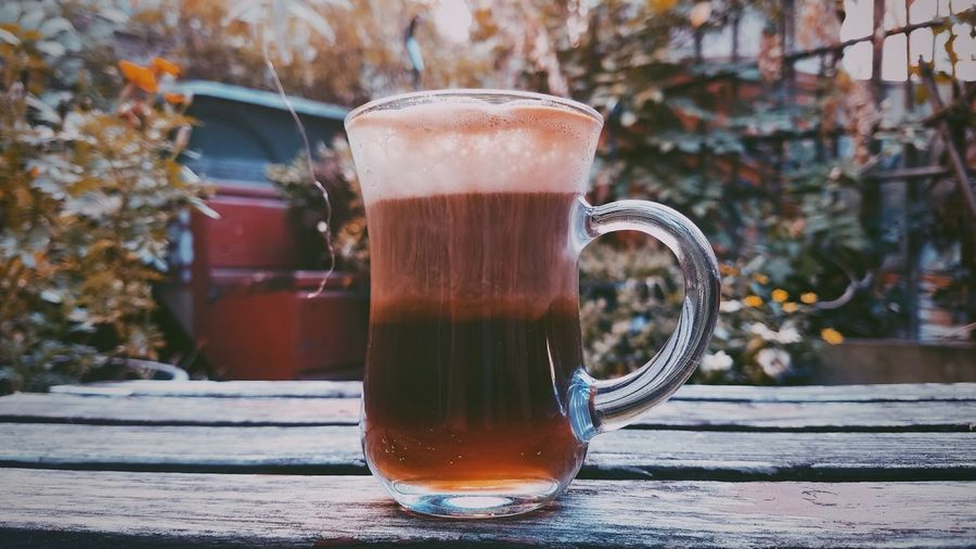 Coffee In Pitcher On Wooden Table At Yard