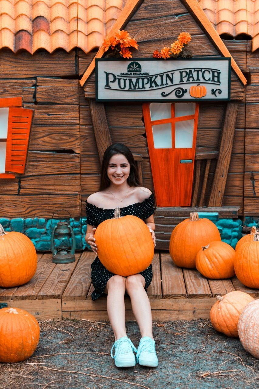 FULL LENGTH PORTRAIT OF A SMILING YOUNG WOMAN STANDING BY PUMPKINS