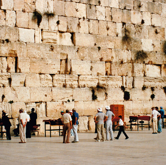 "The Western Wall - Jerusalem, Israel The Western Wall, or ""Wailing Wall"", is the most religious site in the world for the Jewish people. Located in the Old City of Jerusalem, it is the western support wall of the Temple Mount. Thousands of people journey to the wall every year to visit and recite prayers. These prayers are either spoken or written down and placed in the cracks of the wall. The wall is divided into two sections, one area for males and the other for females. It is one of the major highlights in any tour of the Old City. Architecture People Men Women Day Castle History Standing Outdoors Ancient Adult Adults Only Full Length Wailing Wall Temple Mount Travel Destinations Ancient Civilization Large Group Of People Building Exterior Built Structure Old Ruin Saying Prayers Western Wall Of Jerusalem Jewish Peoples"