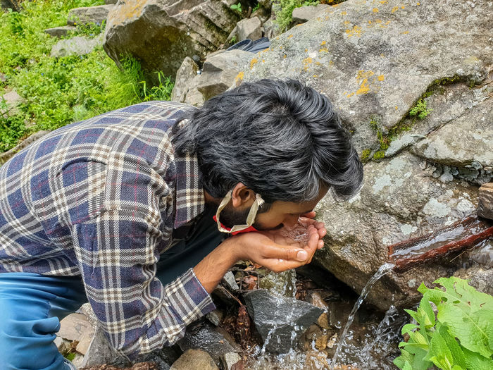 High angle view of man drinking water on rock