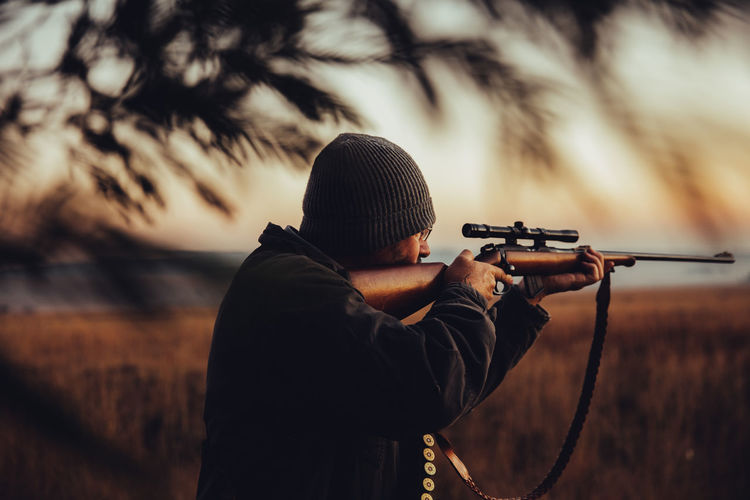 Man Aiming Rifle On Field