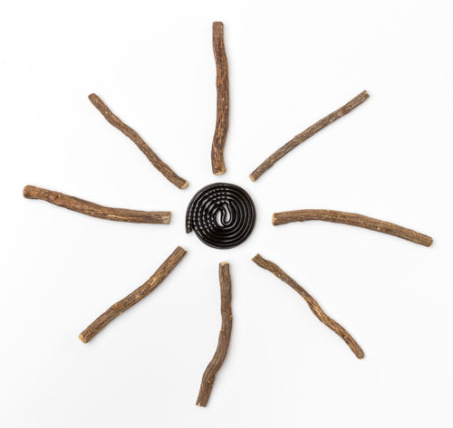 Liqorice roots and black wheel on white background. Top view. Aromatic Ayurveda Bio Biological Black Candy Clock Cold Diet Food Health Healty Herb Herbal Ingredient Isolated Licorice Liquorice Medicinal Medicine Natural Nature Organic Plant Roots
