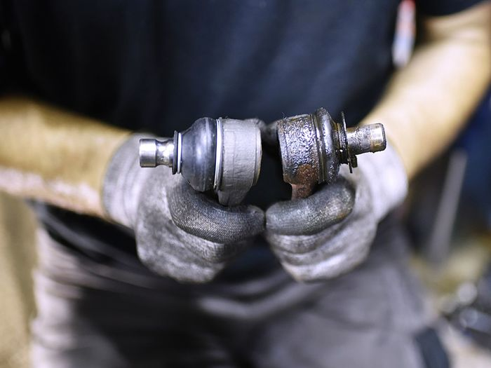 Midsection of mechanic holding car part