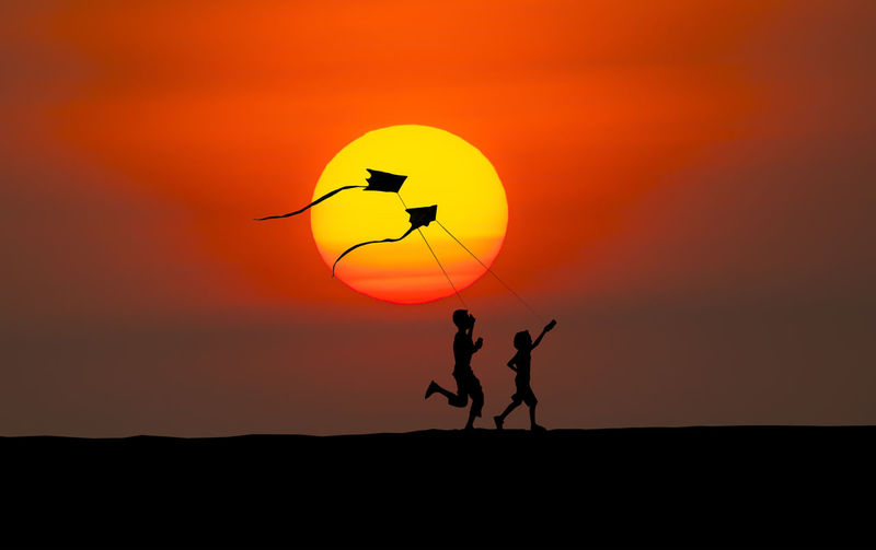 Silhouette kids playing with kite against sky during sunset