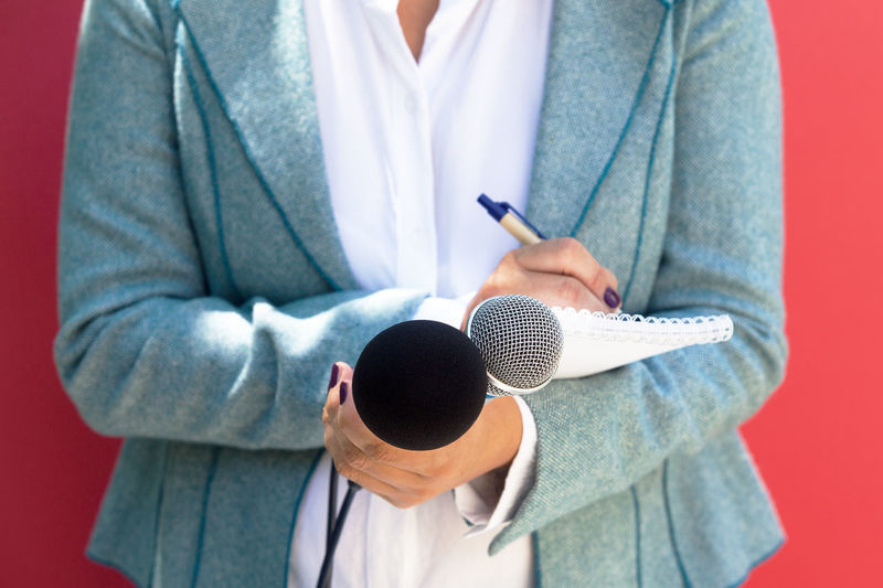 A female reporter at press conference, writing notes, holding microphone Unrecognizable Person Standing Close-up Microphone Writing Pen Taking Notes Notebook Mic Journalist Journalism Reporter Reporting Press Conference News Information News Conference The Media Media Recording Public Communication Multitasking