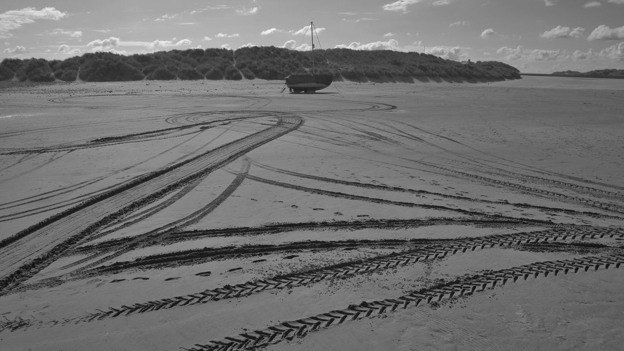 Tire Tracks On Beach Against Sky