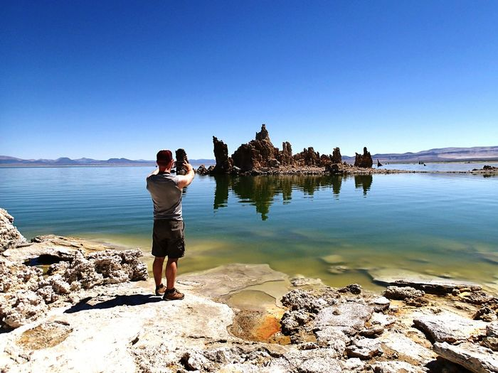 Full length rear view of man photographing sea using camera against clear blue sky
