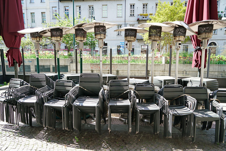 Empty chairs and tables on street in city