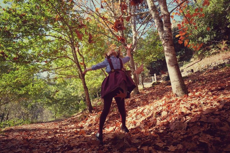 Girl Throwing Autumn Leaves In Forest