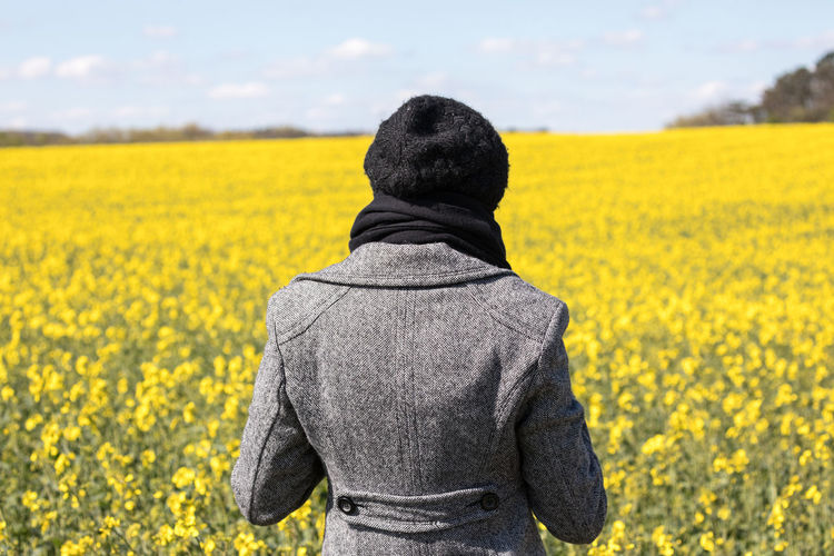 Adult Agriculture Beauty In Nature Cap Coat Day Field Flower Focus On Foreground Jacket Landscape Nature One Boy Only One Person One Woman Only Outdoors People Real People Rear View Sky Standing Sunny Yellow Yellow Flower Oilseed Rape