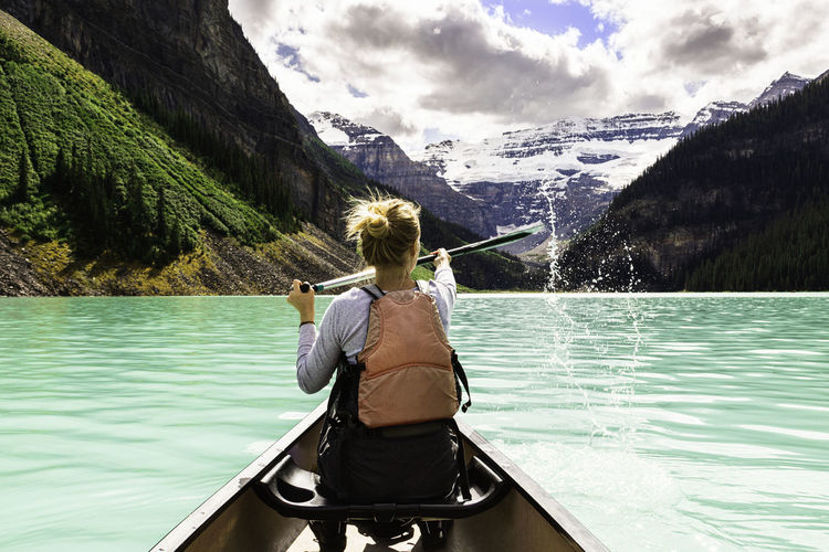Rear view of woman rowing boat on lake
