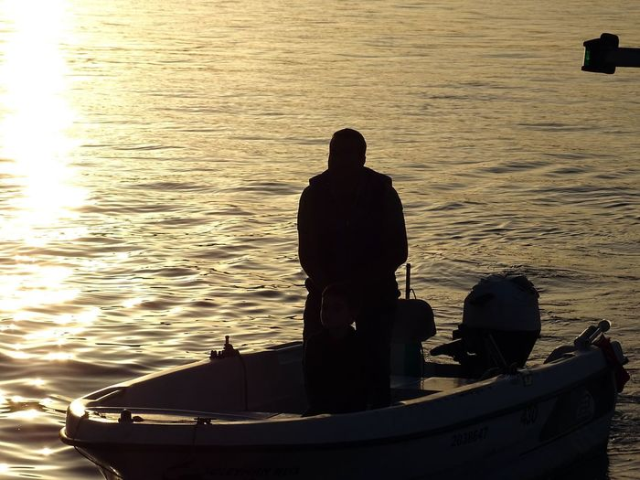 Rear view of silhouette man on boat in sea against sky