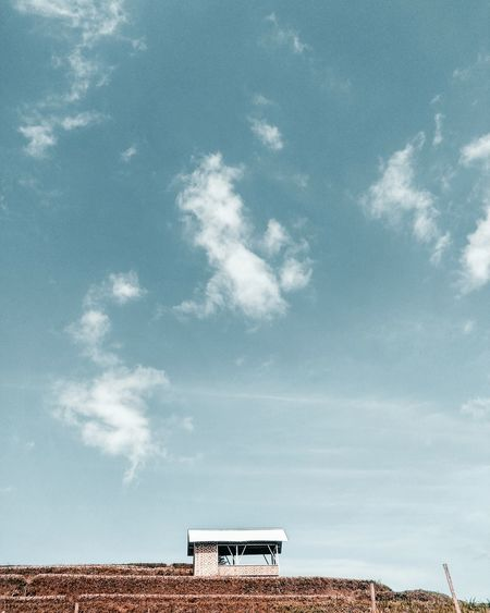 Low angle view of shed against cloudy sky