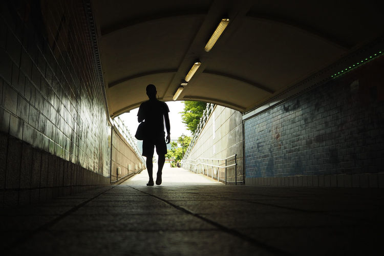 Footpath Leisure Activity Light At The End Of The Tunnel Men One Person Real People Tunnel Underground Walkway Walking Wall Wall - Building Feature