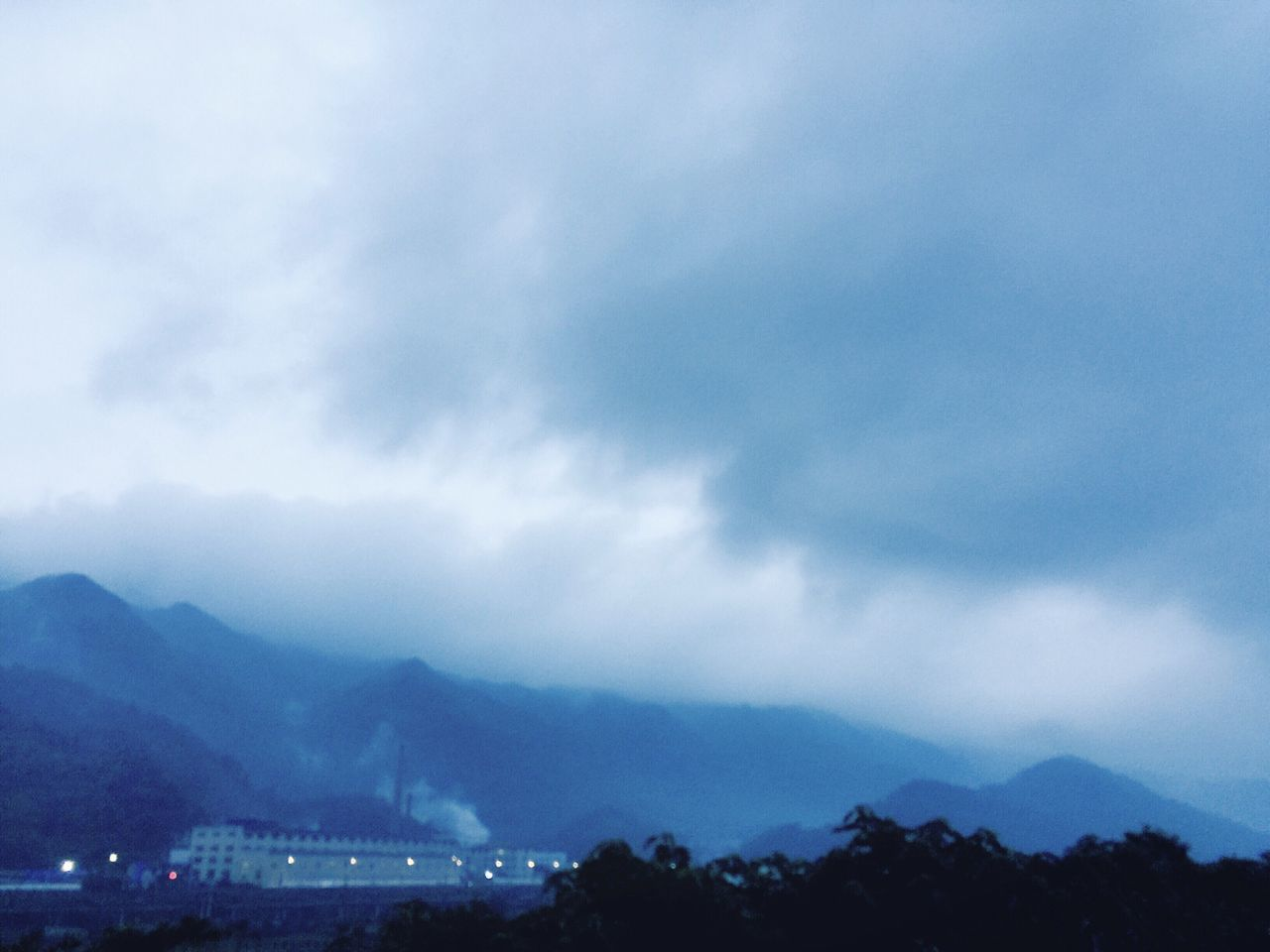 mountain, sky, cloud - sky, beauty in nature, architecture, weather, building exterior, mountain range, no people, nature, scenics, outdoors, silhouette, cityscape, built structure, city, day, range