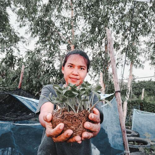 Portrait of woman holding plants