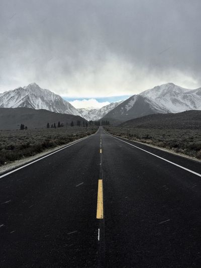 EMPTY ROAD VANISHING IN MOUNTAINS AGAINST CLOUDY SKY