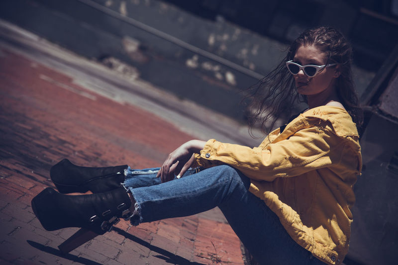 Side view of young woman wearing sunglasses sitting on footpath in city