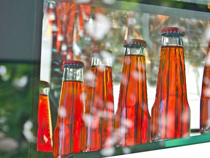 Glass - Material Transparent Container Indoors  Bottle No People Choice Food And Drink Close-up Selective Focus In A Row Display Red Jar Arrangement Glass Still Life Focus On Foreground Business Bistro