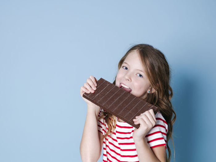 pretty blonde girl with a giant bar of chocolate is posing in front of blue background Girl Child Chocolate Bar BIG Huge Brown Sweet Hold Food Candy Nutrition Unhealthy Teeth Calories Nerves Happy Cocoa Reward Laugh Joy Posen Model Copy Space Concept Energy Sugar Ration Sweet Tooth Nibble Chomp Munch Delicious Good Addictive Intoxication Beautiful Childhood One Person Portrait Girls Offspring Looking At Camera Holding Headshot Indoors  Front View Brown Hair Hairstyle Happiness Long Hair Studio Shot Innocence Casual Clothing Food And Drink Blue Background Temptation