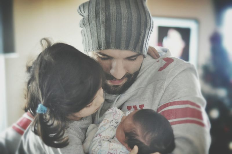 Close-Up Of Father With Daughter And New Born Baby Boy