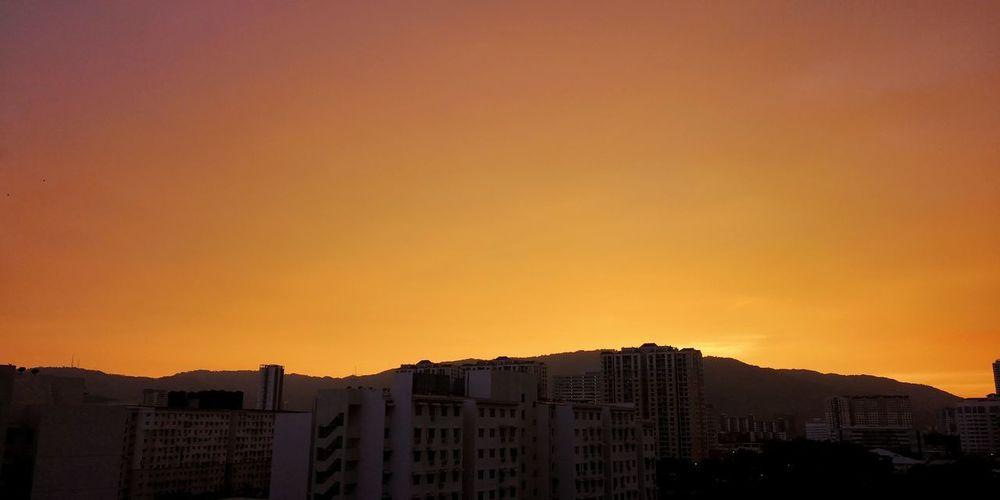 Silhouette buildings against orange sky