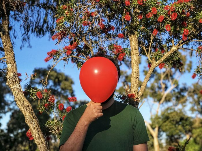 Man holding red balloon against flowering tree.